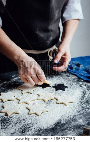 Hands of cook putting cookies to the flour. Vertical studio shot.