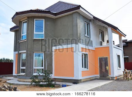 Close up on Painting and Plastering Exterior House Wall. Facade Thermal Insulation and Painting Works During Exterior Renovations