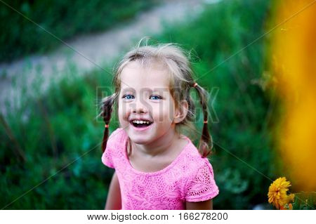 Beautiful blue-eyed girl with two pigtails laughs.