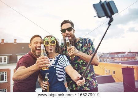 Group Of Three Adults Drinking And Taking Pictures