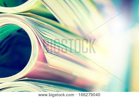 Close up edge of colorful magazine stacking roll with blurry bookshelf background for bublication and publishing concept extremely DOF with vintage retro color tone