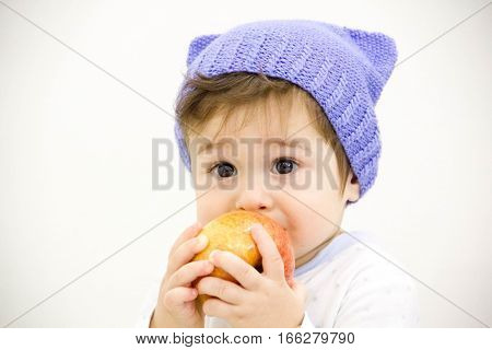Cute baby boy sitting on table with fruits and vegetables and eating an apple isolated on white background