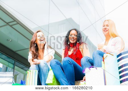 Young women shopping downtown, carrying bags and looking at storefronts.