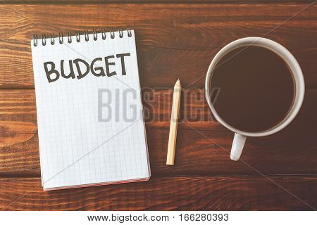 Budget list on notepad and cup of coffee on wooden table. Budget planing concept. Top view. Vintage style, retro toned picture.