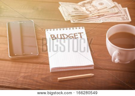 Notepad with word Budget, mobile phone, cup of coffee and money on rustic wooden table. Business concept, budget planing of businessmen or family. Retro toned image.