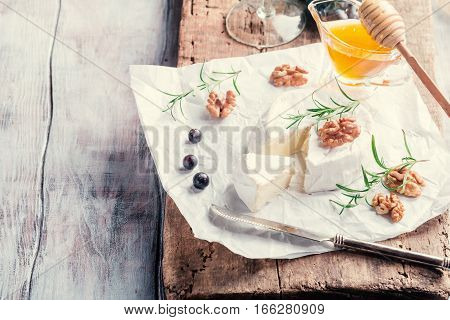 Brie cheese and a slice on a wooden board with nuts, honey and rosemary.