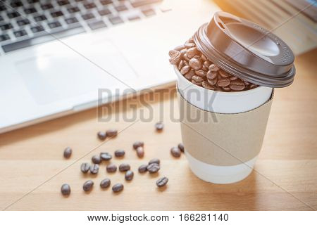 A paper cup of full roasted aroma coffee beans with blurred background of some fallen coffee beans on wooden board and laptop business concept.