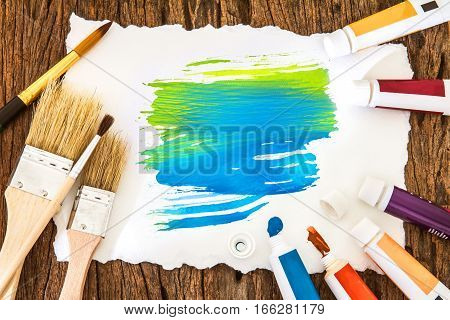 Art brush and blue yellow watercolor painted with white paper art on wooden background summer color tone