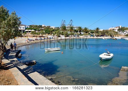 AGIOS NIKOLAOS, CRETE - SEPTEMBER 17, 2016 - Small boats moored in St Nicolas Bay with tourists relaxing on the beach to the rear Agios Nikolaos Crete Greece Europe, September 17, 2016.