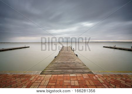 Long exposure with silk water and storm over Albufera with pier, Valencia