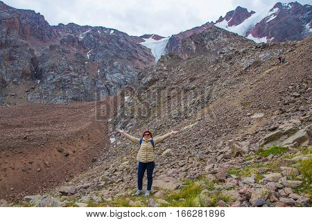 Aged sport woman in sunglasses are standing on the rocks near the snow peak with glacier Tien Shan mountains Almaty Kazakhstan 2016
