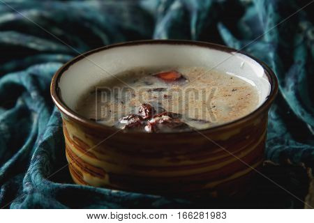 Traditional Indian masala tea in ceramic cup with spices to milk. Dark batskground
