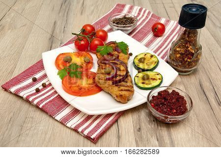 appetizing piece of roasted meat on the grill with vegetables and spices. horizontal photo.
