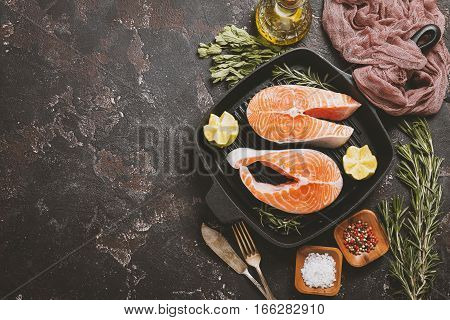 Fresh raw salmon steak, lemon, rosemary and spices on grill frying pan over dark rustic concrete background, top view with copy space. Ingredients set for making healthy dinner. Healthy diet concept.