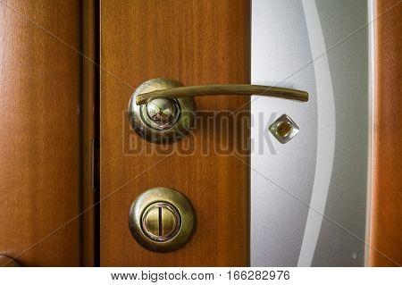 Close-up of hand holding metal bronze doorknob on wooden door