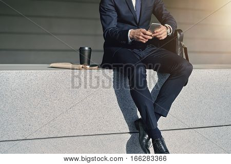 Crop Businessman Sitting At Street With Phone