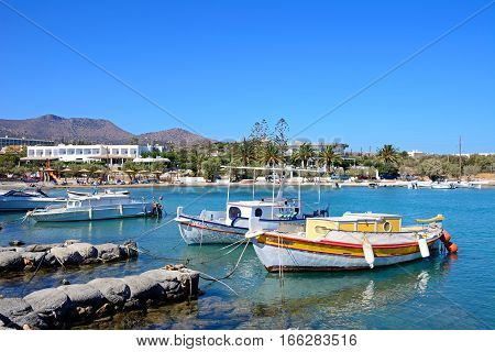 AGIOS NIKOLAOS, CRETE - SEPTEMBER 17, 2016 - Fishing boats moored in St Nicolas Bay with the beach to the rear Agios Nikolaos Crete Greece Europe, September 17, 2016.