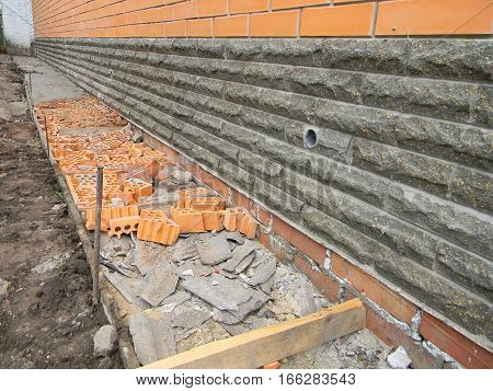 Building foundation waterproofing. Building new house. New construction waterproofing basement walls from outside with detail of a pavement to walk.