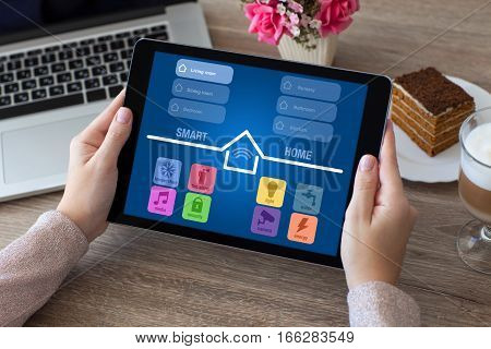 woman hands holding tablet computer with app smart home on screen in room