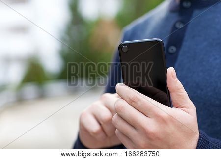 man holding black touch phone in the street