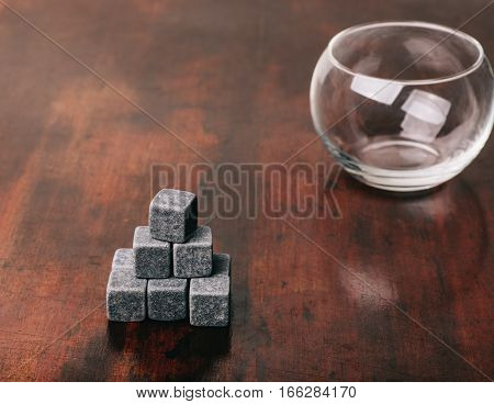 Gray whiskey rocks on a table in mahogany. In the background is a glass cup.