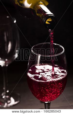 Pouring rose wine into glass on black background