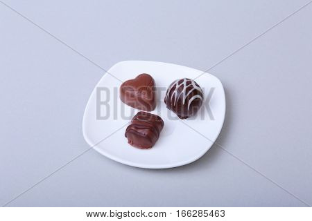 delicacy handmade chocolate pralines on white saucer