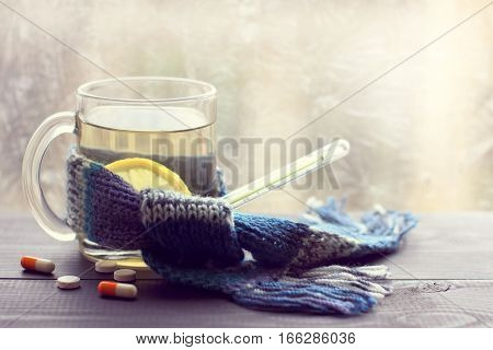 infusion lemon in the transparent mug beside thermometer and tablets on the background of a winter window / hot drink for convalescence