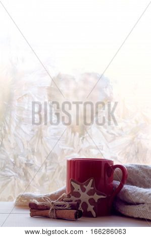 warming drink in a red mug thawed frozen window in the form of a heart symbol / hot power of love