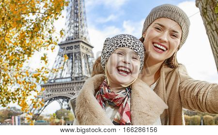 Mother And Child Taking Selfie While Sitting On Parapet In Paris