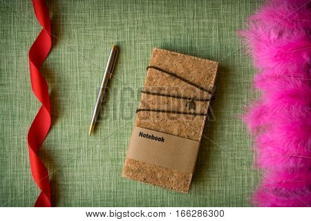 Cork notebook on fabric background with craft supplies