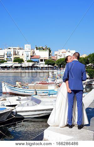 AGIOS NIKOLAOS, CRETE - SEPTEMBER 17, 2016 - Young bride and groom sharing a kiss in the port Agios Nikolaos Crete Greece Europe, September 17, 2016.