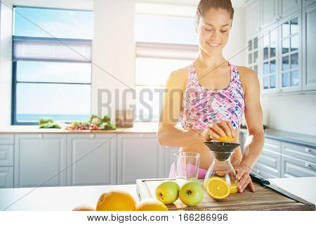 Young Healthy Woman Squeezing Juice From Orange
