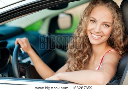 Portrait of Smiling Young Woman in her Car