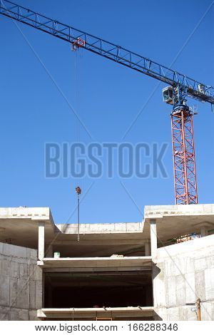 Big hoisting tower crane and top section of modern construction building over cloudless sky