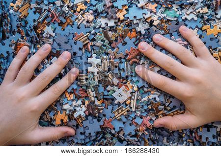 Children's hands on Jigsaw puzzle color background