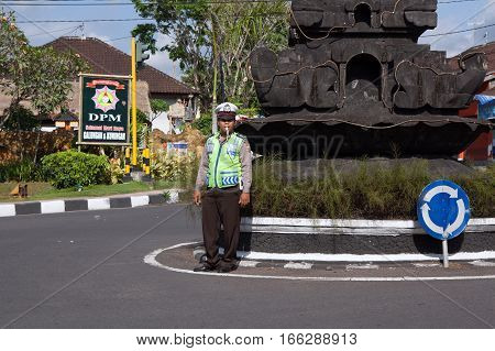 BALI ,INDONESIA - AUGUST 30,2012: Road policeman controls the traffic of vehicles