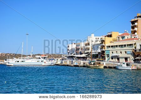 AGIOS NIKOLAOS, CRETE - SEPTEMBER 17, 2016 - Boats in the harbour with waterfront restaurants to the right hand side Agios Nikolaos Crete Greece Europe, September 17, 2016.
