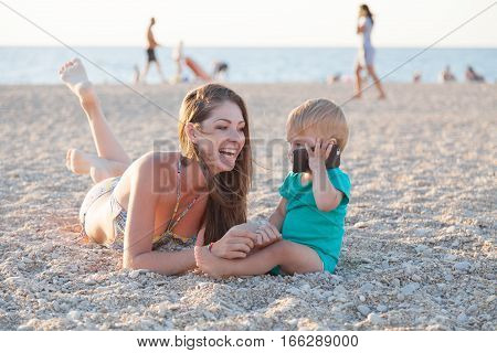 mom and boy talking on the phone on the beach