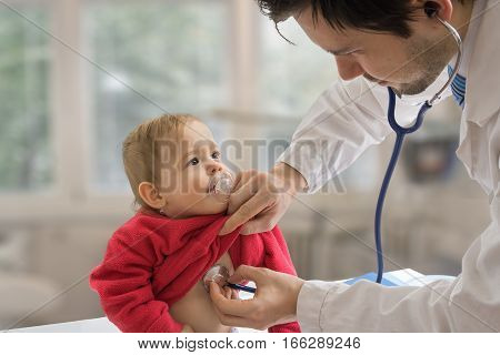 Pediatrician doctor is examining child with stethoscope.
