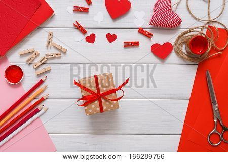Valentines day holiday handmade or wedding decorations. Present in gift box creating, hearts, craft paper, paint and diy tools on white wood. Above view, flat lay