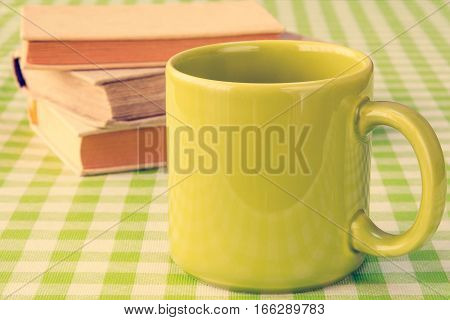Green mug with books on the table.