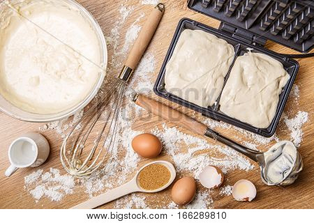 Making waffles at home - waffle iron, batter in bowl, sugar and eggs. Cooking background.