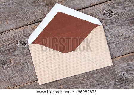 Open brown envelope lying on wooden background