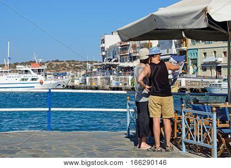 AGIOS NIKOLAOS, CRETE - SEPTEMBER 17, 2016 - Tourists looking at a restaurant menu along the harbour waterfront Agios Nikolaos Crete Greece Europe, September 17, 2016.