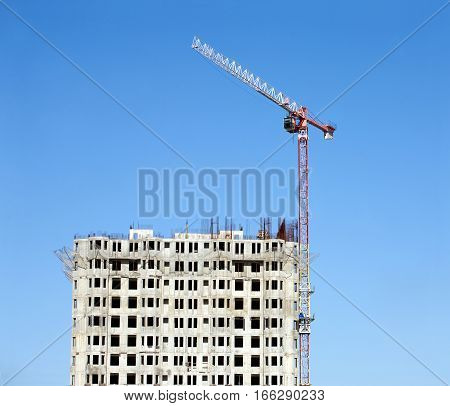Big hoisting tower crane and top section of modern construction building over cloudless sky vertical view