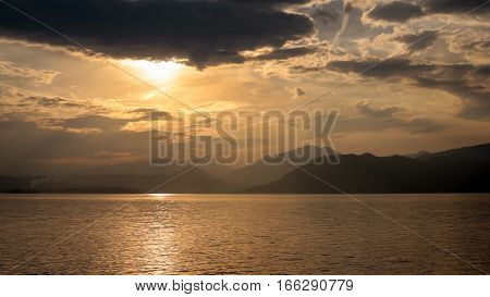 A sunset view of the Italian Alps over the calm waters of Lake Garda Italy at dusk.