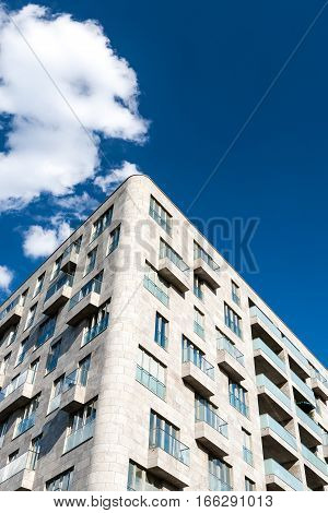 Detail of a contemporary high rise apartment block in central Berlin Germany offset against a rich blue sky and fluffy white clouds providing copy space.