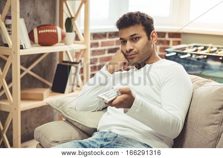 Attractive Afro American man is bored using remote control while watching TV at home