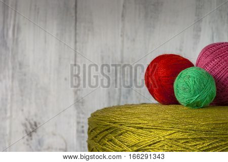 Reel and tangles of colored thread on a background of a wooden wall
